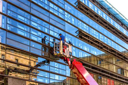 Workers in construction cradle washing windowsl of skyscraper.