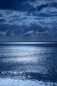 seascape of deep blue sea and sky lit by moonlight