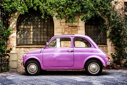 Pink Fiat 500 Oldtimer typical italian parking in front of a wall