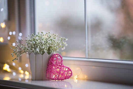 Pink wicker heart and bouquet of beautiful white gypsophila near window in the daylight, bokeh lights on background.
