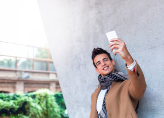 Outdoor portrait of modern young man with mobile phone in the street making a selfie