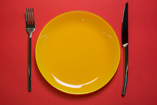Empty yellow plate with fork and knife on red background top view