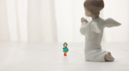 Image of a surprised little girl who saw a figure of a praying angel. Concept: Christmas miracle story & winter holidays.