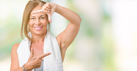 Beautiful middle age woman wearing sport clothes and a towel over isolated background smiling making frame with hands and fingers with happy face. Creativity and photography concept.