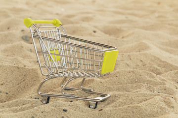 Empty shopping cart on tropical white sand beach day noon light. Image for summer vacation shopping and summer sale concept for promotion. Close up. Soft focus.