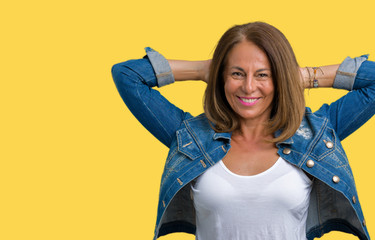 Beautiful middle age woman wearing casual denim jacket over isolated background Relaxing and stretching with arms and hands behind head and neck, smiling happy
