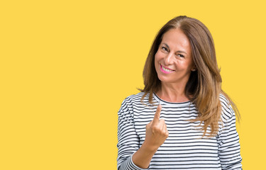 Beautiful middle age woman wearing stripes sweater over isolated background Beckoning come here gesture with hand inviting happy and smiling