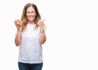 Middle age hispanic woman eating pizza slice over isolated background pointing and showing with thumb up to the side with happy face smiling