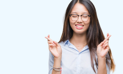 Young asian business woman wearing glasses over isolated background smiling crossing fingers with hope and eyes closed. Luck and superstitious concept.
