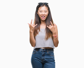 Young asian woman wearing sunglasses over isolated background shouting with crazy expression doing rock symbol with hands up. Music star. Heavy concept.
