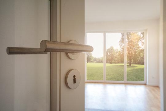 Neubau-Immobilie Umzug in neue Wohnung - Tür in modernes Wohnzimmer mit Blick auf Garten