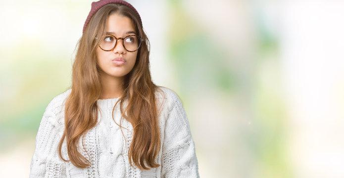 Young beautiful brunette hipster woman wearing glasses and winter hat over isolated background making fish face with lips, crazy and comical gesture. Funny expression.