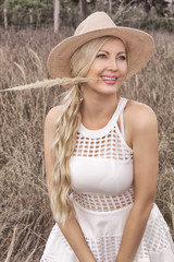 Beautiful young blonde in a hat posing in the field of ears.