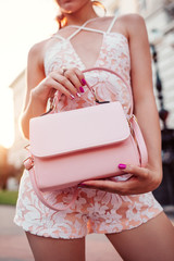 Close-up of stylish female handbag. Fashionable woman holding beautiful accessory and wearing sexy outfit outdoors.