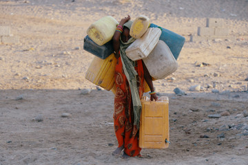 Girl carries jerry cans to fill them up with drinking water at a camp sheltering displaced people from the Red Sea port city of Hodeidah near Aden, Yemen
