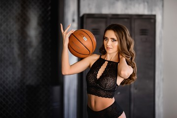 Beautiful girl in black lingerie with a basketball ball.