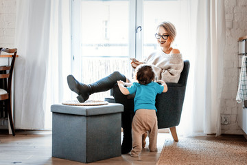 Young mother with mobile phone sitting in armchair and little toddler boy stay next to her on a flloor. Home interior decoration