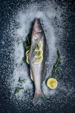 Overhead view of fish with rosemary, salt and lemons