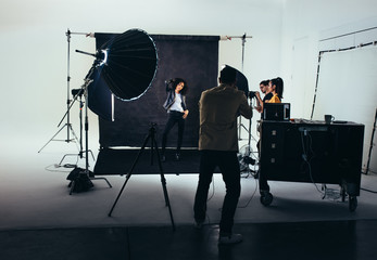 Photographer with his crew during a photo shoot in studio.