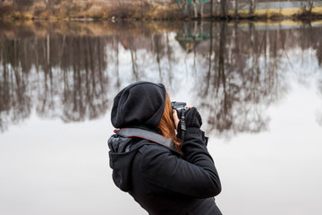 girl taking pictures on camera during a trip to the lake cold late autumn reflection of trees, sky, forest