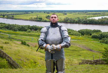 knight in armor stands against the background of native open spaces, forests and a river. Knightly armor and weapon. Semi - antique photo.
