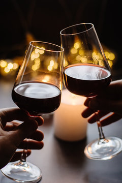 Two glasses of wine  red in hand on the background candle and  garlands
