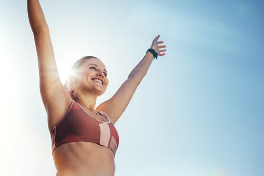 Smiling fitness woman doing workout raising her arms