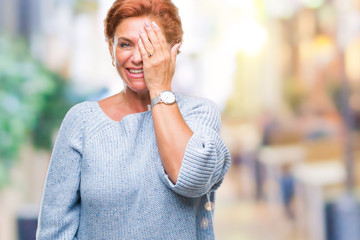Atrractive senior caucasian redhead woman wearing winter sweater over isolated background covering one eye with hand with confident smile on face and surprise emotion.