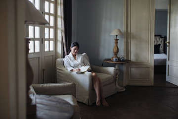 Beautiful Asian woman sitting in a hotel room and writing in her notebook.