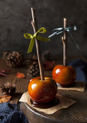 Two toffee apples with almond flakes and natural wooden sticks