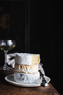 Stack of cheese on plate with white wine