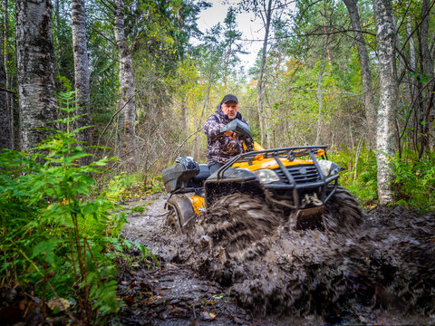 ATV overcomes the swamp. A man travels on ATV. Yellow quad bike. Off-road travel. A man drives an SUV. Yellow ATV.