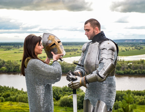 The lady puts on her knight a helmet. Knightly armor and weapon. Semi - antique photo.