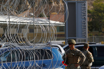 U.S. Marines stand guard next to a barricade with concertina wire at the border between Mexico and the U.S. in Tijuana