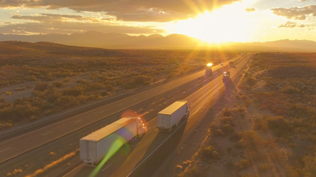 AERIAL: Cars and semi trucks driving on busy highway at summer sunset