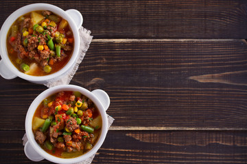 Delicious hamburger soup with vegetables: peas, corn, carrots, potatoes, tomatoes and green beans (can be cooked with frozen vegetables). overhead, horizontal