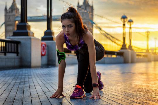 Sportliche Frau in Start Position beim Training bei Sonnenaufgang in der Stadt