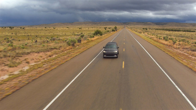 AERIAL: Black SUV car driving on wet empty countryside road in bad rainy weather