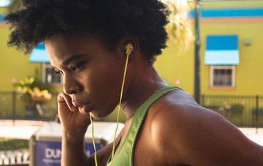 Strong african american woman in green running shirt listening to her workout playlist