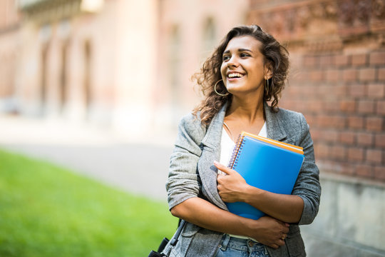 Pretty cheerful latin american student smiling at camera carrying notebook on campus at college