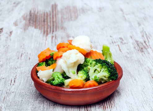 Vegetables served on a plate surrounded byrustic background