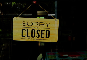a wooden closed sign hanging on window of a shop with words read sorry we are closed, please come back again