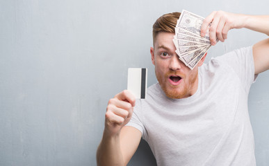 Young redhead man holding dollars and credit card scared in shock with a surprise face, afraid and excited with fear expression