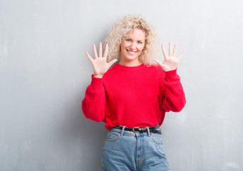 Young blonde woman with curly hair over grunge grey background showing and pointing up with fingers number ten while smiling confident and happy.