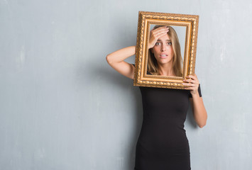 Beautiful young woman over grunge grey wall holding vintage frame stressed with hand on head, shocked with shame and surprise face, angry and frustrated. Fear and upset for mistake.