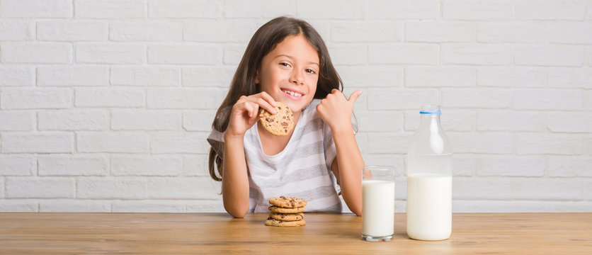 Young hispanic kid sitting on the table drinking milk and eating chocolate cooky pointing and showing with thumb up to the side with happy face smiling