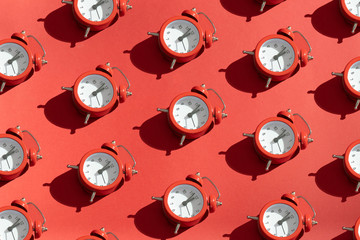 The red clock is lined up in rows on a bright red background. Festive Christmas or New Year concept. Minimalism in the style of pop art. Copy space