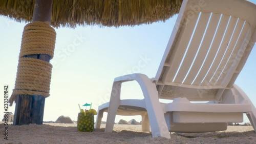 5x Lounge Chair : Lounge chair under a palm umbrella at a tropical beach resort in