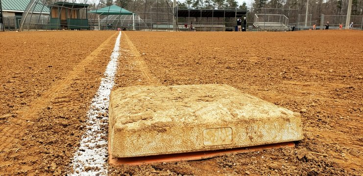 Dirty first base on a baseball field looking toward home and third base dugout.  Bright white foul line on clay diamond. Low angle. Little league baseball field in public park.