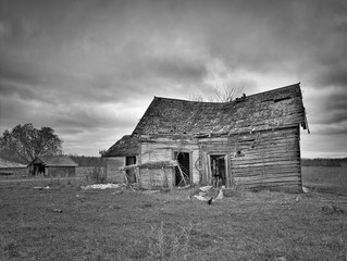 Black and white image of dreary abandoned dilapidated farm house with cloudy skies in northern Minnesota